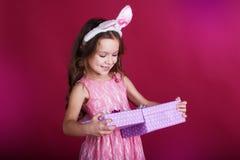 Flickan bär rosa färgklänningen, och kaninen gå i ax med Royaltyfri Fotografi