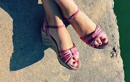 Flickan bär rosa skor på sjösidan Arkivfoto