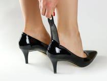 Flickan bär svarta skor med en sked closeup Royaltyfria Foton