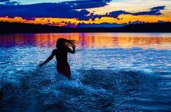 Flickan badar i en sjö på natten Royaltyfria Foton
