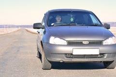 Flickan bak hjulet av en bil Royaltyfria Foton