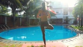 Flickan balanserar i yogaposition vid pölen i morgonbak stock video