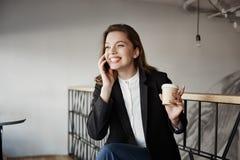 Flickan berättar rolig berättelse till hennes coworker Stående av härligt smart europeiskt kvinnasammanträde i kafé som dricker k royaltyfri foto