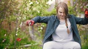 Flickan besprutar sig med myggaimpregneringsmedlet, i trädgårds- sommardag