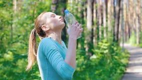Flickan bevattnade sig med vatten från en flaska lager videofilmer