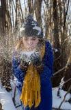 Flickan blåser av snön från händerna i vinterskogen som hon bär ett purpurfärgat lag och en grå hatt arkivbild