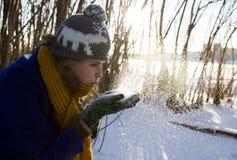 Flickan blåser av snön från händerna i vinterskogen som hon bär ett purpurfärgat lag och en grå hatt arkivfoto