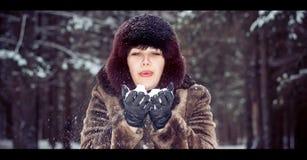 Flickan blåser bort snön från Royaltyfri Foto