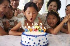 Flickan blåser ut stearinljus på familjfödelsedagberöm royaltyfri foto