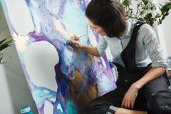 Flickan blandar målarfärger i paletten som går att starta konstterapi Fotografering för Bildbyråer