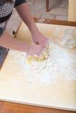 Flickan blandar vid handen vattnet, mjöl och ett ägg Arkivfoto