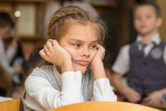 Flickan borrade på skolasammanträde på ett skrivbord på omvänt arkivfoton