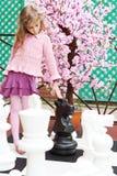 Flickan bredvid den konstgjorda körsbärsröda blomningen trycker på stora schackstycken Royaltyfri Fotografi