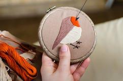 Flickan broderar en fågel med en häftklammer DIY-begrepp, hobbyer, kreativitet, kläder och inregarnering arkivfoto