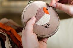 Flickan broderar en fågel med en häftklammer DIY-begrepp, hobbyer, kreativitet, kläder och inregarnering Arkivbild