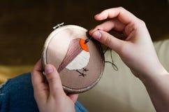 Flickan broderar en fågel med en häftklammer DIY-begrepp, hobbyer, kreativitet, kläder och inregarnering Arkivfoton