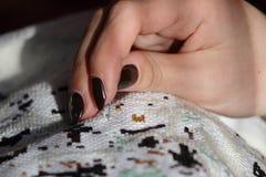 Flickan broderar markeringshäftklammeren på en vit kanfasbild Fotografering för Bildbyråer