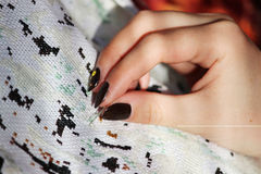 Flickan broderar markeringshäftklammeren på en vit kanfasbild Arkivbild