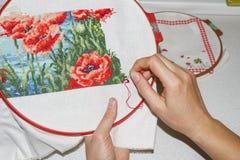 Flickan broderar nära övre för bild Händer, visare, tråd och broderi Hobbyhus med egna händer Hand-gjorda produkter Fotografering för Bildbyråer
