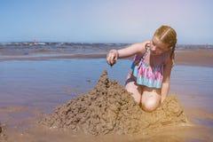 Flickan bulding sandslottar på stranden royaltyfria bilder