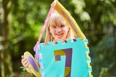 Flickan bygger ett modellhus från pusselstycken royaltyfria foton