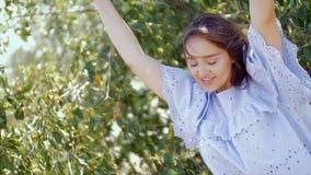 Flickan dansar framme av kameran på en bakgrund av grön lövverk av träd arkivfilmer