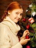 Flickan dekorerar julgranen Royaltyfria Bilder