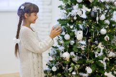 Flickan dekorerar julgranen Arkivbilder