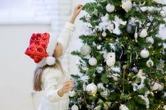 Flickan dekorerar julgranen Royaltyfri Bild