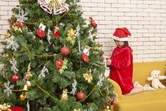 Flickan dekorerar julgranen Ungar som dekorerar Chris royaltyfri foto