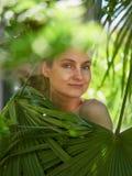 Flickan dolde bak palmbladen royaltyfri foto