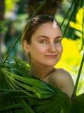 Flickan dolde bak palmbladen royaltyfri bild