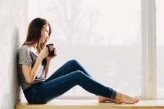 Flickan drömmer vid fönstret Arkivfoton