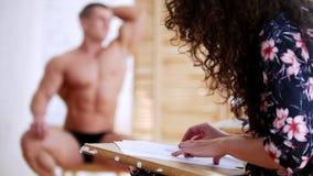 Flickan drar en muskulös shirtless grabb på en kanfas lager videofilmer