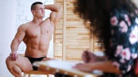 Flickan drar en muskulös shirtless grabb på en kanfas stock video