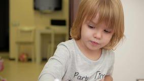 Flickan drar en röd markör på papper stock video