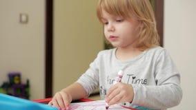 Flickan drar en röd markör på papper arkivfilmer