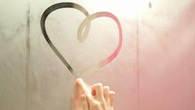 Flickan drar ett finger som drar en hjärta på en snabb dimmig spegel arkivfilmer