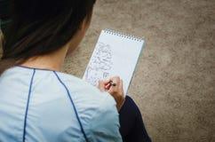 Flickan drar i en anteckningsbok på gatan Närbild fotografering för bildbyråer