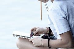 Flickan drar i ett anteckningsboksammantr?de p? trottoaren royaltyfri bild