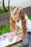 Flickan drar med blyertspennor i skolan parkerar Begreppet av skola, kamratskap, teckning, studie, hobby royaltyfri bild
