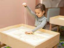 Flickan drar med sand på en ljus tabell royaltyfria bilder