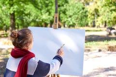 Flickan drar röda målarfärger på staffli arkivfoton