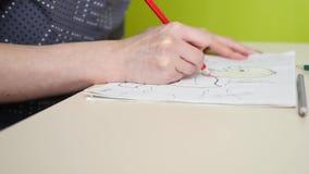 Flickan drar teckningar med kulöra blyertspennor arkivfilmer