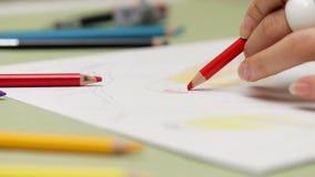 Flickan drar vänsterhänt med den röda blyertspennan på papper, detaljerad sikt i slowmotion lager videofilmer