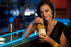 Flickan dricker en coctail i nattklubb arkivfoto