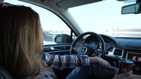 Flickan dricker en varm drink, ser ut fönstret, kopplar av i bilen 4K långsam mo arkivfilmer