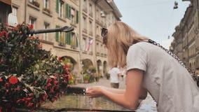Flickan dricker från en dricka springbrunn i gatorna av Bern switzerland arkivfilmer