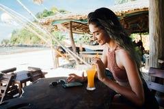 Flickan dricker fruktsaft och kontrollerar telefonkafét på semester med en sikt av havet och stranden Arkivfoto