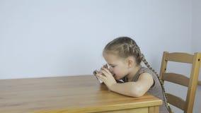 Flickan dricker ivrigt vatten, medan sitta i köket lager videofilmer